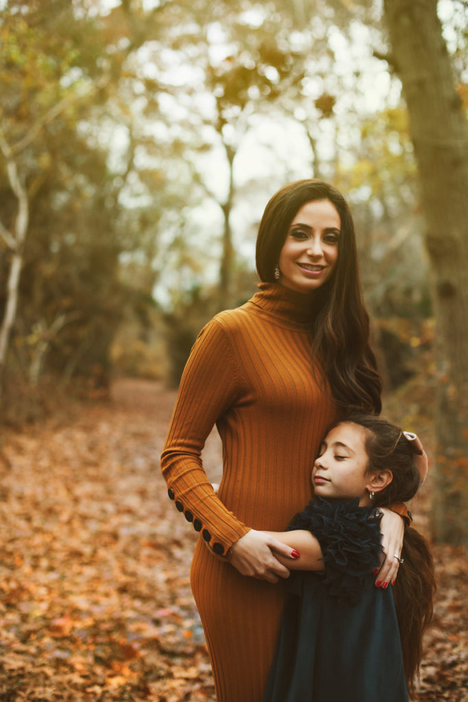 lifestyle photgraphy, elegantly dressed mother and daughter embrace standing in fall leaves in forest