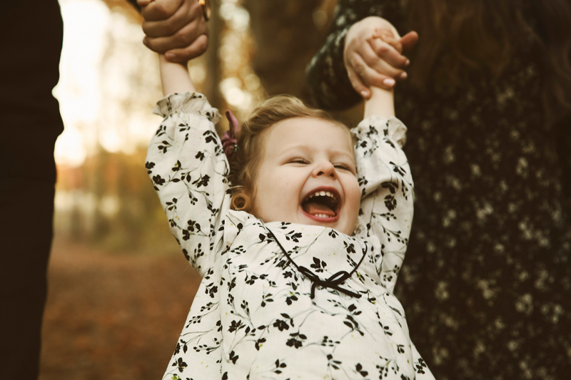 lifestyle photograph, small girl swings from parents arms with big smile on her face